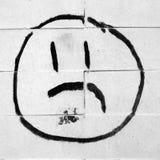 Desenho infeliz da cara em uma parede de tijolo Fotografia de Stock Royalty Free
