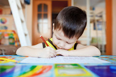 Desenho ocupado do rapaz pequeno usando penas de feltro em casa Fotos de Stock Royalty Free