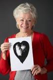 Desenho sênior da tinta da terra arrendada da mulher do coração Fotos de Stock Royalty Free