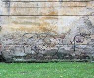 Desenho velho e envelhecido dos grafittis da cor na parede Fotos de Stock