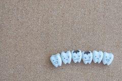 Desenhos animados bonitos dos dentes da saúde e do ícone deteriorado no fundo de madeira da cortiça para a educação das crianças Foto de Stock