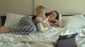 Desenhos animados de observação da mãe e da filha no tablet pc video estoque