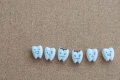 Desenhos animados dos dentes da saúde e do ícone deteriorado no fundo de madeira da cortiça para a educação das crianças Fotos de Stock Royalty Free