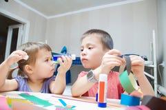 Desenvolvimento de crianças - irmão e irmã que fazem o ofício imagens de stock