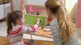 Desenvolvimento de infância adiantada Tempo de aprendizagem da menina com brinquedo do pulso de disparo em casa video estoque