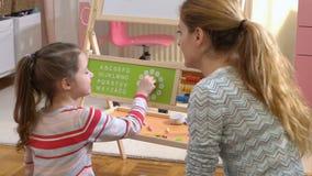 Desenvolvimento de infância adiantada Tempo de aprendizagem da menina com brinquedo do pulso de disparo em casa vídeos de arquivo