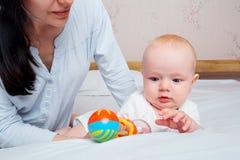 Desenvolvimento do bebê Bebê pequeno que joga com um entusiasta do brinquedo foto de stock