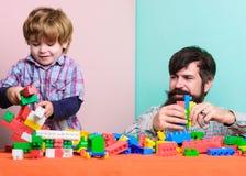 Desenvolvimento e educa??o da puericultura Jogo do filho do pai O pai e o filho criam construções coloridas com os tijolos fotografia de stock