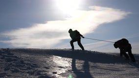Deseo del trabajo en equipo de ganar Escaladores en una ayuda de la cuerda una subida del amigo al top de la colina Silueta de vi almacen de metraje de vídeo