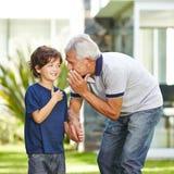 Deseo susurrante de abuelo en el oído del nieto Fotos de archivo libres de regalías