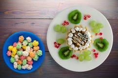 Deser tortowi i owocowi winogrona, kiwi, granatowiec na woode Zdjęcie Stock