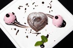 Deserowa fondan czekolada z lody na białym talerzu na czarnym tle Wyśmienity Francuski czekoladowy deserowy fondan obraz stock
