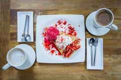 Deserowego lody truskawkowa krepa i gorący napój w sklep z kawą Zdjęcia Royalty Free