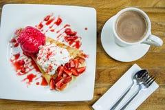 Deserowego lody truskawkowa krepa i gorący napój w sklep z kawą Fotografia Royalty Free