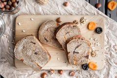 Deserowy żyto chleb z wysuszonymi morelami, orzechy włoscy i przycina kłamstwa na czarnym drewnianym stole z papierem Kilka kawał zdjęcia royalty free