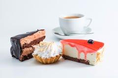 Deserowy ustawiający z filiżanki kawą na białym tle Trzy kawałka torta dżemu mousse cheesecake czekoladowa czerwona babeczka makr Fotografia Stock