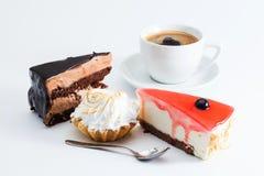 Deserowy ustawiający z filiżanki kawą na białym tle Trzy kawałka torta dżemu mousse cheesecake czekoladowa czerwona babeczka makr Obrazy Royalty Free