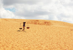 Desert. Vietnamese woman carrying water in desert stock image