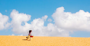 Desert. Vietnamese woman carrying water in desert stock photo