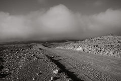 Through the Desert. A dirt road running through a stone desert lit by the setting sun in monochrome Royalty Free Stock Images