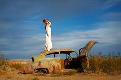 Desert beauty. Bride in the desert on old car Stock Photo