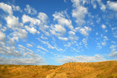 Desert and blue sky. Blue sky, white clouds, and desert hill Stock Image