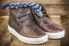 Desert boots with socks on wood stock photography