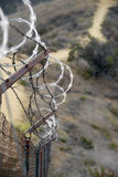 Desert Border Fence. A wire fence in hilly scrubland topped with razor wire Stock Photo