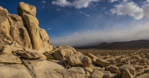 Desert Boulders and Approaching Storm. Dark clouds gather over distant mountains in the Mojave Desert of southern California royalty free stock photography