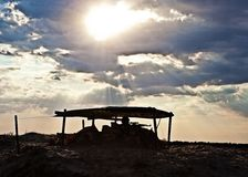 Desert checkpoint. Military desert checkpoint with armed sentinel in the sunset stock photo