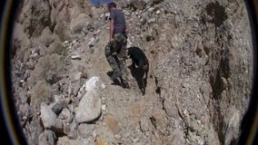Desert Climb with Dog 2. Wind Caves Borrego Desert California stock footage