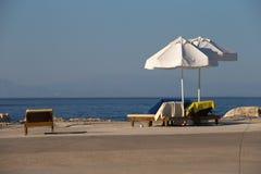 Desert concrete beach. Empty deckchairs with towels under umbrellas on a deserted concrete beach Stock Photography