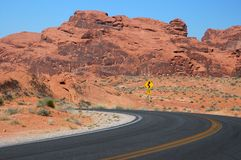 Desert Curve. Highway Veers Left in Rugged Red Desert Royalty Free Stock Photos