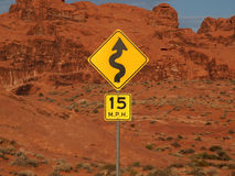 Desert Curves. Ahead highway sign with cliff backdrop Stock Photography