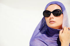 Desert Dream. A young woman with a head scarf and sunglasses in a desert Stock Image