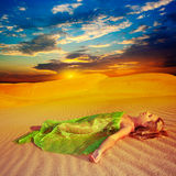 Desert dreams. Beautiful woman sleeping in the middle of desert Royalty Free Stock Photos