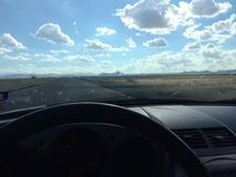 Desert Drive. Driver POV clouds sky car interior stock image