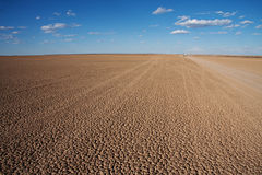 Desert dry pan. Verneukpan, South Africa, large flat desert pan where land speed records are attempted with car disappearing in the distance Stock Images