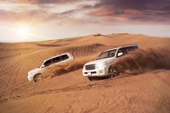 Desert Dune Bashing. Two 4x4 vehicles bashing side to side through the desert dunes in the evening sun stock images