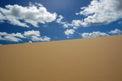 Desert dune and white clouds Royalty Free Stock Photos