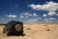 Desert expedition. A jeep driving in the desert royalty free stock image