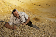Desert fashion shot. Young man lying supine, head covered by jumper, on the sloping yellow desert sands Royalty Free Stock Image