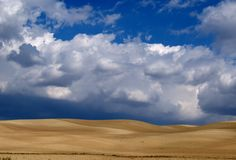 Desert field and sky with clouds. Spectacular blue with white clouds on a deserted field heaven Royalty Free Stock Images