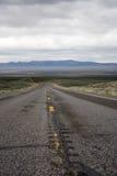 Desert Highway. A worn highway road through the desert in Nevada, beneath a cloudy sky Stock Photo