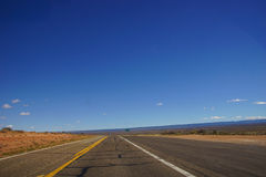 Desert highway with horizon Stock Photos