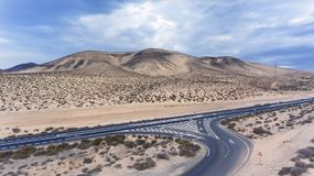 Desert highway junction, road markings, volcanic mountains. Aerial view of desert road joining highway in arid, barren mountains area of Fuerteventura, Canary Royalty Free Stock Image