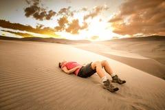 Desert Hiker. Tired hiker girl lying on the desert sand royalty free stock image