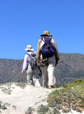 Desert Hiking. A couple with backpacks hiking barefoot through the flowering desert Stock Images