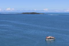 Desert island and a boat, south Pacific Royalty Free Stock Photo