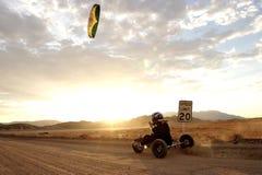 Desert Kite Buggying. A man kite buggies on a deserted desert road at sunset Stock Photo